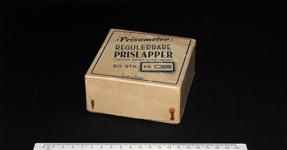"""Regulerbare prislapper (""""Prisometer"""") med eske.  Form:  Esken og lokket kvadratiske, nummerlappene 10-kantete,  """"Kr.""""-lappene rektangulære i grunnform,  de """"blanke"""" lappene rektangulære."""