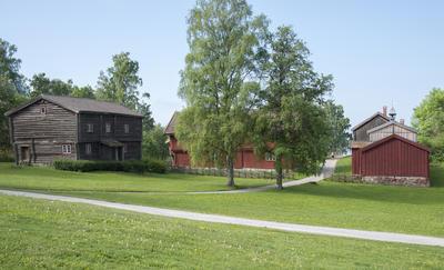 Hedmarkstunet består av en grå tømmerbygningn i to etasjer til venstre i bildet, midt på ser vi to bjørker og til høyre en rød, plankebeslått bygning.