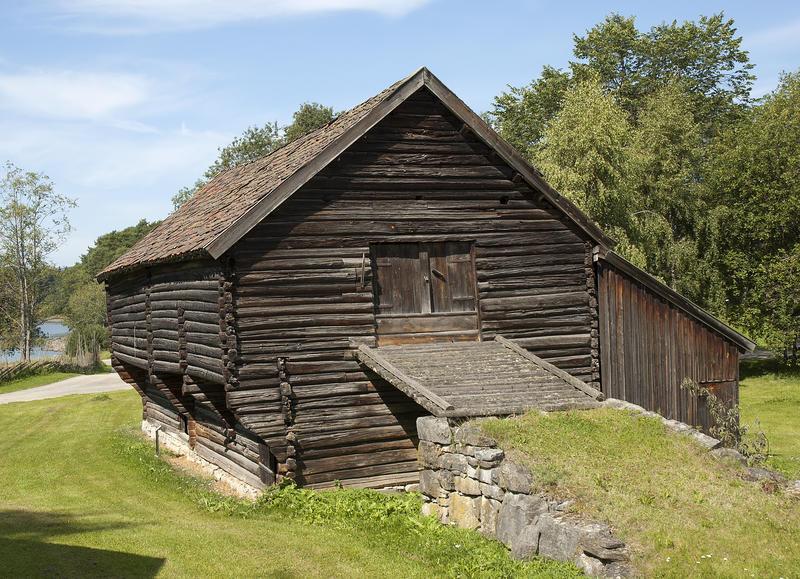 Stor tømmerstall med utbygd andreetasje og låvebru opp til låvedør i gavlveggen. (Foto/Photo)