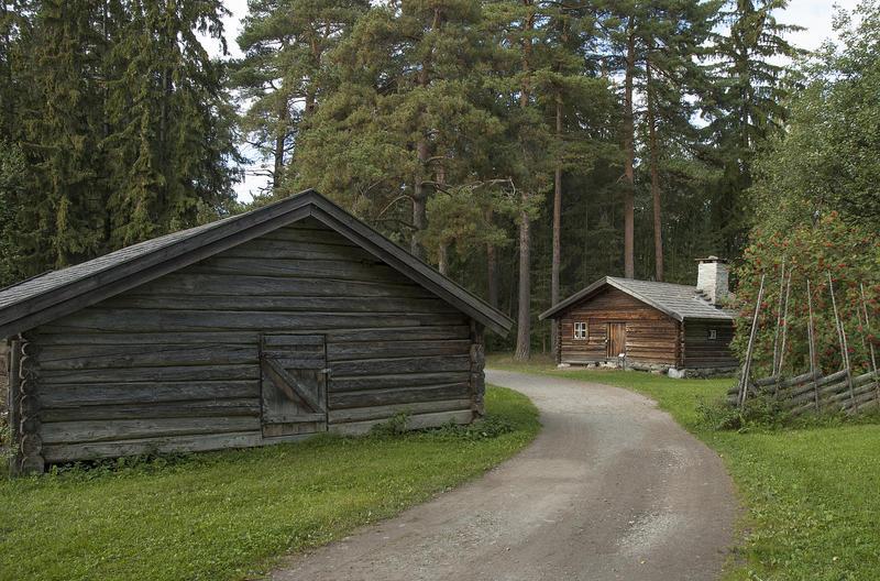Grusveg som leder inn mellom et grått tømmerhus til venstre og et brunt tømmerhus med flistak til høyre. Rundt husene ligger høye furutrær.