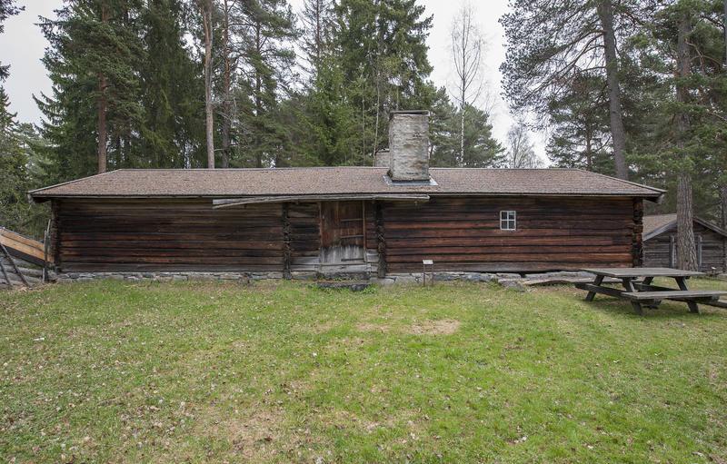 Langt størhus i brunlig tømmer, med stor plen og et parkbord utenfor. (Foto/Photo)