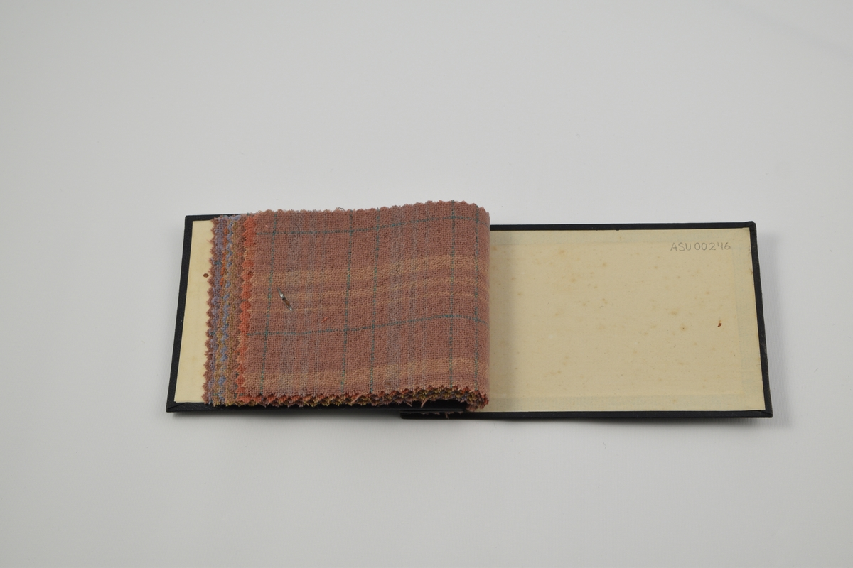 Prøvebok med 8 prøver. Tynne ullstoff med striper eller ruter. Denne prøveboken inneholder flere ulike designnummere av kvalitetnr. 10. Alle stoffer er merket med en rund papirlapp festet med metallstifter hvor nummer er påskrevet for hånd.  Stoff nr. 10/25 (rosa med striper), 10/26 (fiolett med ruter), 10/27 (beige med ruter), 10/28 (blå med ruter), 10/29 (beige med striper), 10/30 (rosa med ruter), 10/31 (orange med ruter), 10/32 (rosa med ruter).