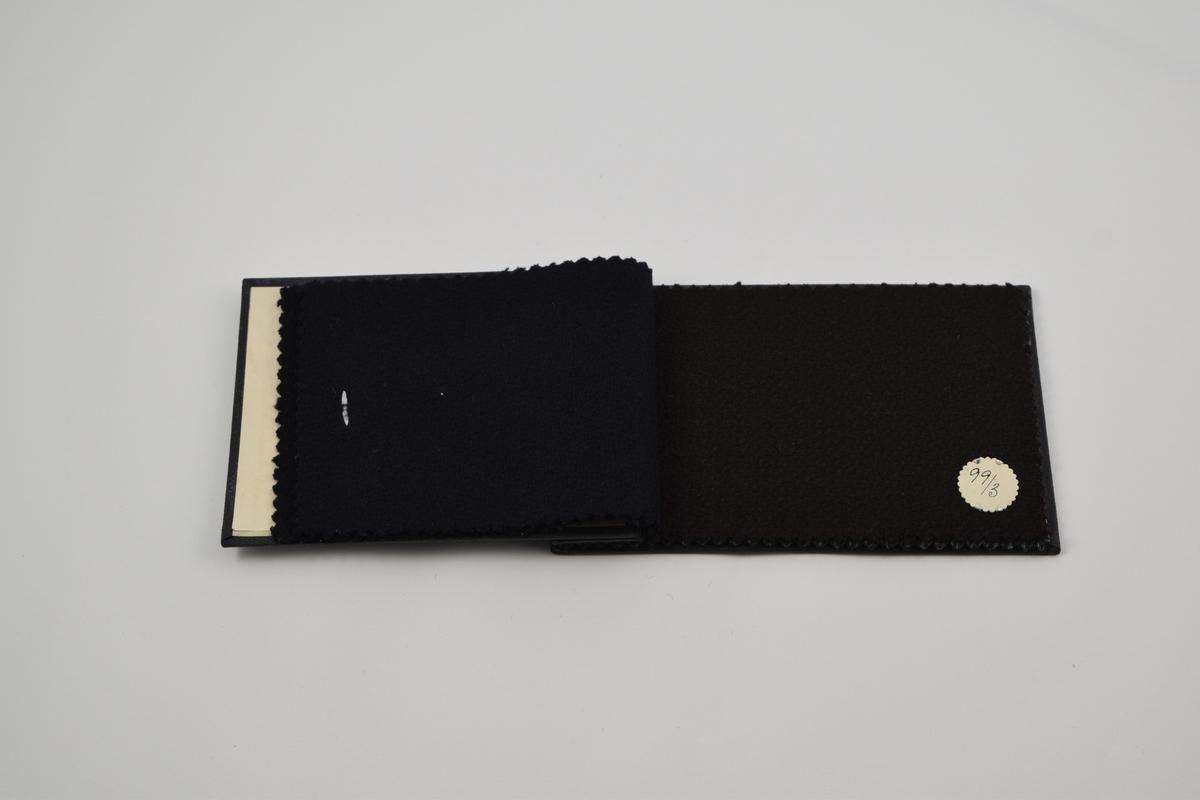 Prøvebok med 5 prøver. Middels tykke ullstoff ensfargede eller med diskret mønster. Alle stoffer er merket med en rund papirlapp festet med metallstifter hvor nummer er påskrevet for hånd.  Stoff nr. 99/1 (sort), 99/2 (sort), 99/3 (brun), Kåpe/1 (grå med skrå striper), Kåpe/4 (grå med skrå striper).