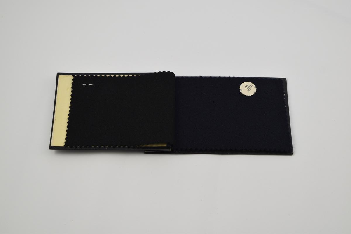 Prøvebok med 4 prøver. Middels tykke ensfargede ullstoff. Alle stoffer er merket med en rund papirlapp festet med metallstifter hvor nummer er påskrevet for hånd.  Stoff nr. 99/1 (sort), 99/2 (mørk blå), 99/3 (mørk grønn), 99/4 (mørk brun).