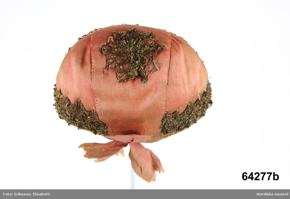 """A.Doppåse B. Mössa C. Förvaringsask  A. Doppåse av kattun, smårutig brun botten med tryckt blommönster i krapprött och rosa, blått, grönt och gult med mörka konturer. Dekorerad med applicerade motiv, överst ett rosa hjärta av sidenbitar och -band med påsydda silver-och guldspetsar, därunder 2 rundlar av siden och sidenband, den övre rosa, den undre röd krans och gul mitt, runt dessa en slinga av rosa sidenband med påsydda guldspetsar. I nederkanten blått sidenbrokadband och ett smalt rosa band fastsytt i sicksack. Nederst en fastsydd bomullsfrans i brunrosa. Fodrad med fin oblekt linnelärft Anm. Sidenbanden sköra, metallspetsarna skrynklade. I nederkanten där det blå brokadbandet är delvis bortnött skymtar kattunet i nyskick med ursprungliga färger och glättad yta. Kattunmönstret är detsamma som på flera andra folkliga plagg i samlingarna. Mönstret trycktes bl.a av Sickla kattuntryckeri grundat 1729. Se  Henschen: Kattuntryck, 1720-1850, Nord.mus förlag 1992,  sid 148 ff. B. Mössa  enl. Huvudliggare: av rosa siden prydd med guldspetsar, fodrad med vitt linne. Sidenatlas, sydd av tre stycken, Gulspetsen löper runt kanten och dessutom formad som en stjärna mitt på hjässan. till modellen som en bindmössa med liten snibb fram och rosa nackrosett.  C. Ask i svepteknik, grönmålad märkt i botten: """"Ursprungligen från Långsele by där dräkten gått i arv inom en släktlinje troddes det i ett par hundra år."""" (1891) (Tygtrycket är dock inte äldre än från omkr. 1730) Berit Eldvik nov. 2005  Inventering Sesam 1997-1998: /.../ C. Ask, oval. Botten och lock av barrträ, svep av lövträ, med falsar. Lockets svep fästat med dymlingar av trä, bottensvepet fästat med nubbar av metall. Hopfästning av svepen med rottågor, kedjesöm, två rader. Lockets ovansida och svepen grönmålade. Bottenskivans undersida med ristat bomärke, möjligen """" P E """" samt  """" 1428 """". Agnetha Blomberg 1997"""