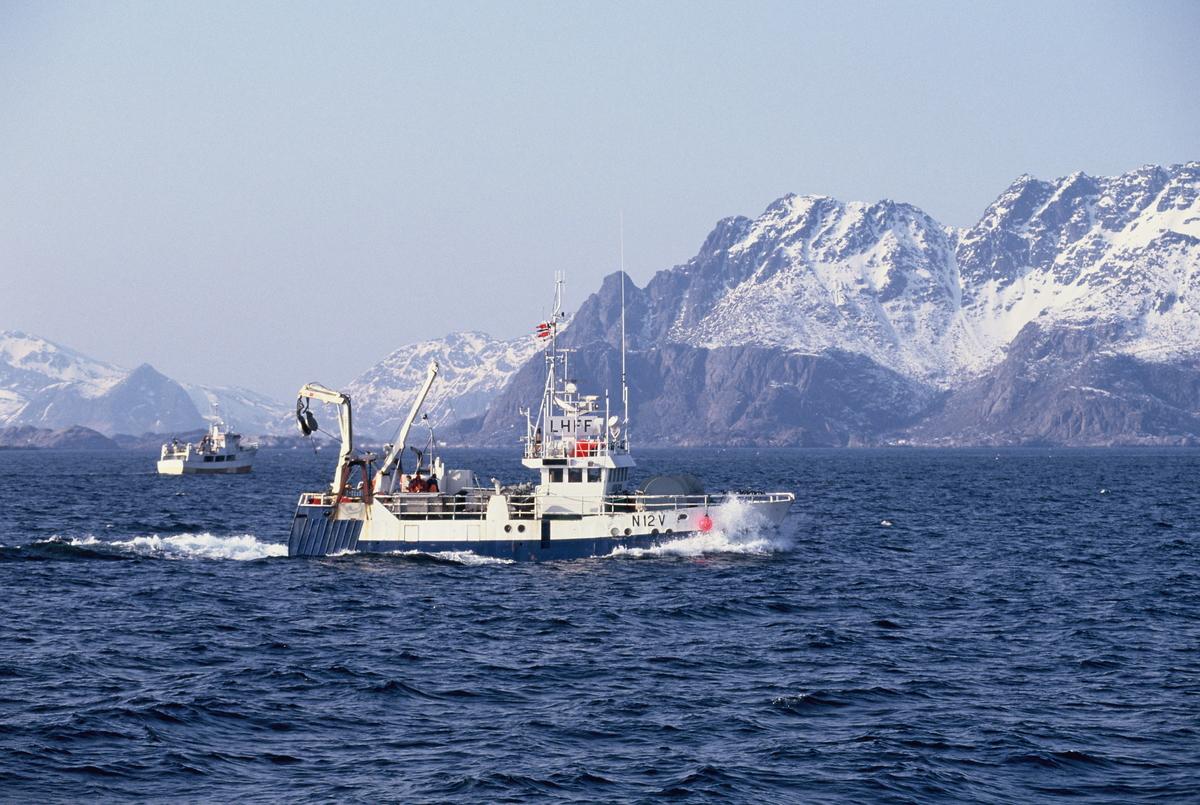 To fiskebåter på havet, Lofoten, med Lofotveggen i bakgrunnen