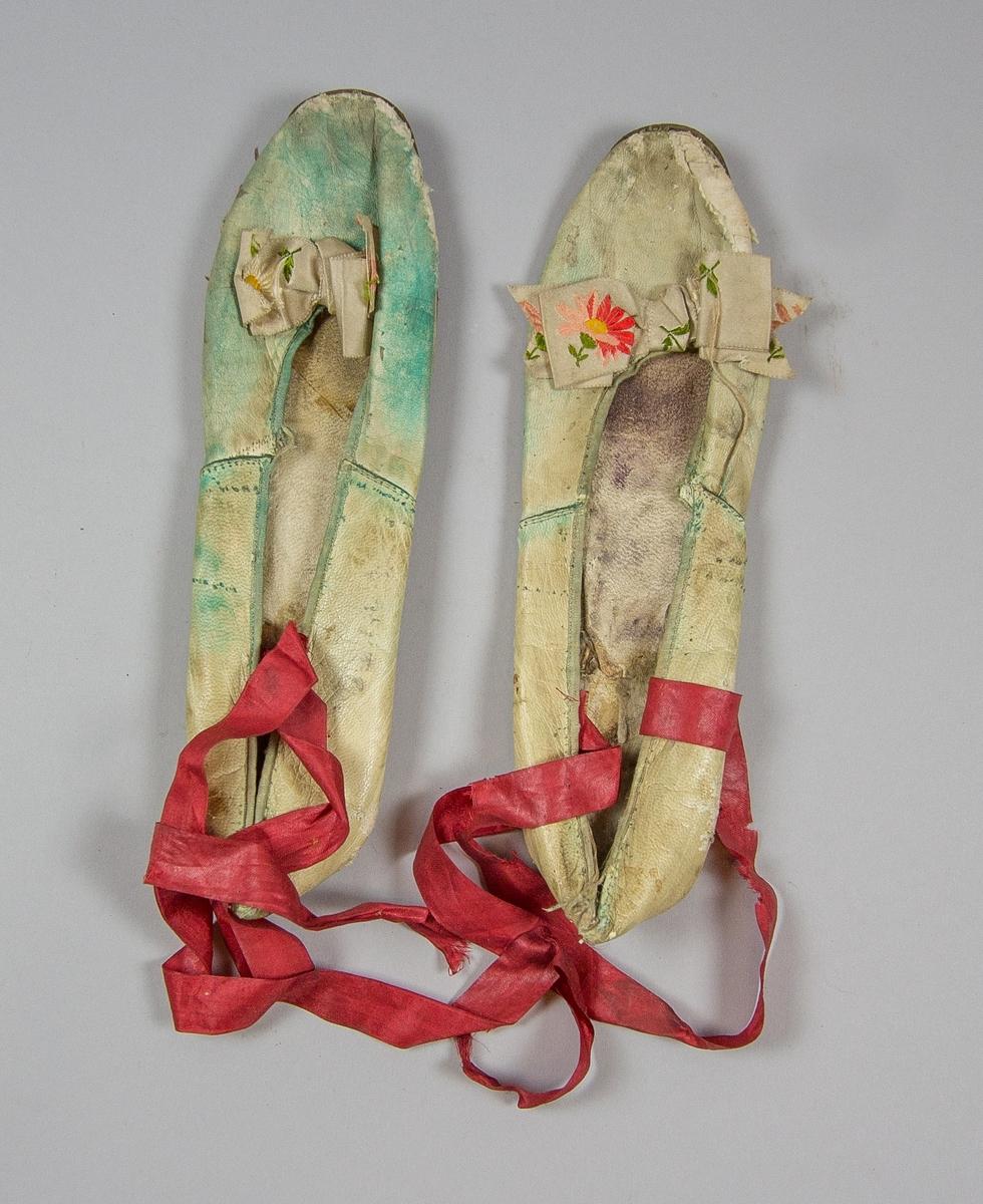 Skor, dam, ett par av skinn. Rester av grön färg. Rosett av siden med broderade blommor. Röda sekundära knytband. Klack borttagen.