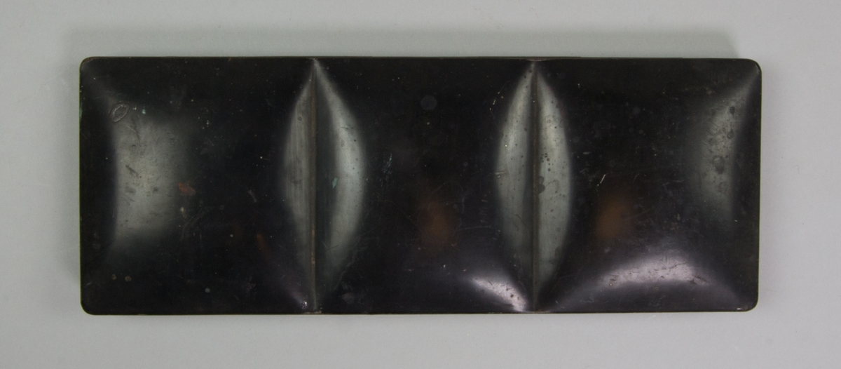 Färglåda rektangulär av svartmålad plåt, med uttag för tummen. Invändigt fällock och fackindelning, delvis med lösa färgkoppar av porslin. Rester av färg. I lådan ligger även ett pärlband med röda och genomskinliga glaspärlor.