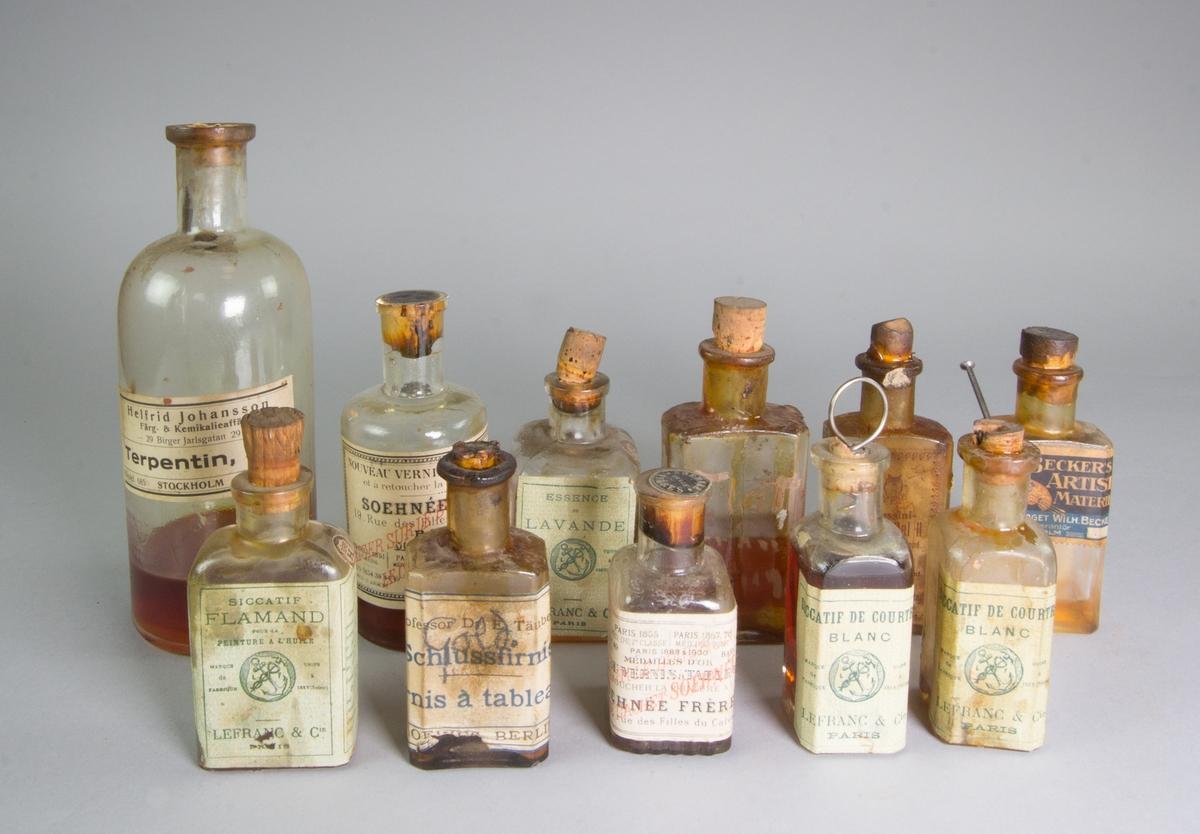 Flaskor av glas, 11 st, med skiftande innehåll som tavelfernissa, sikativ, terpentin med mera.