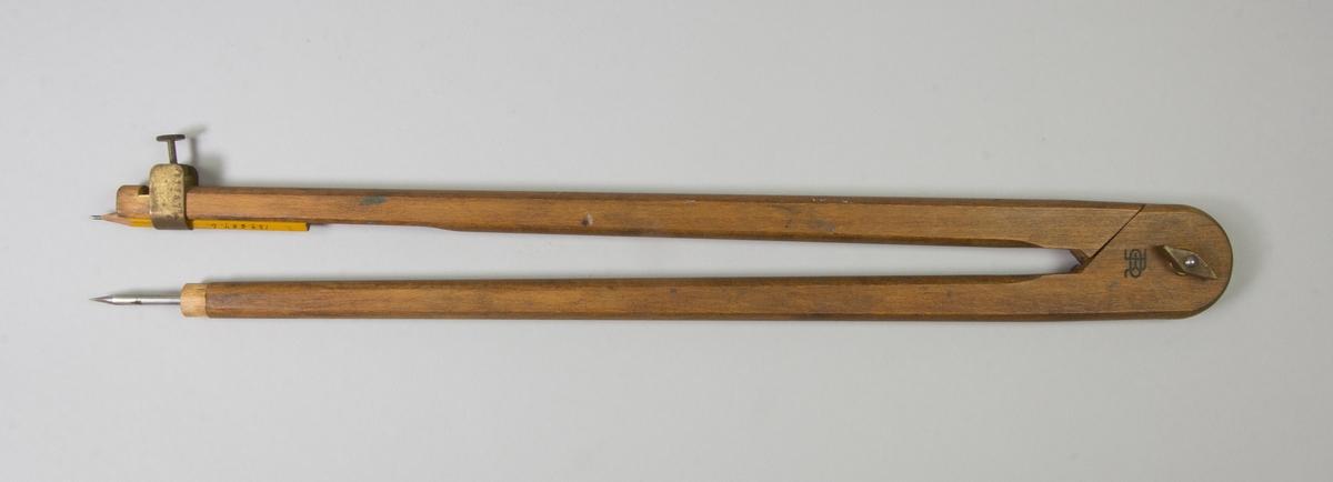 Passare av trä med stift av järn och hållare av mässing för blyertspenna. Blyertspenna instucken i hållare på ena benet.