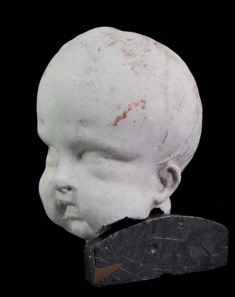Studiemodell av gips föreställande barnhuvud.