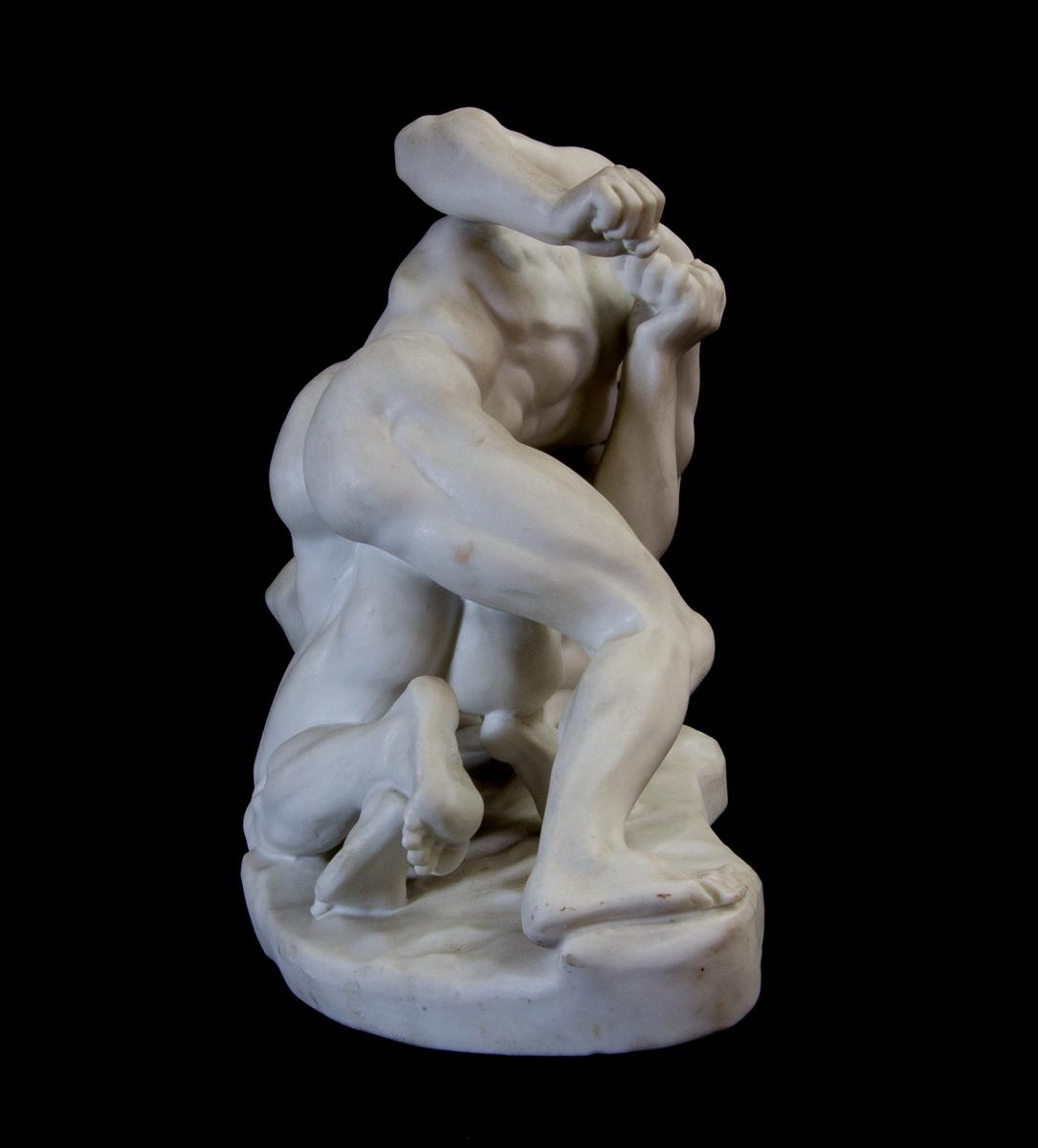 Studiemodell av parian föreställande två unga nakna män som brottas. Oval platta.