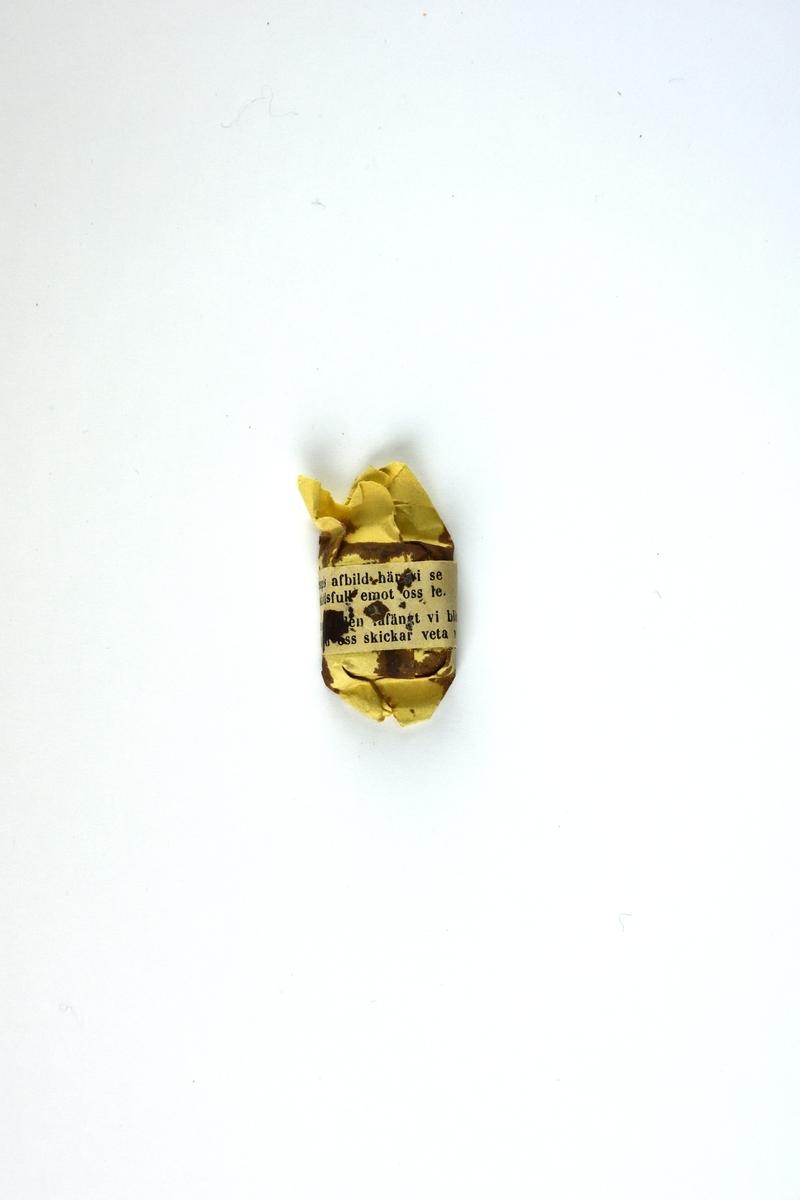 Konfekt i ljusgult papper. Vit gördel med inskrift runt konfekten.
