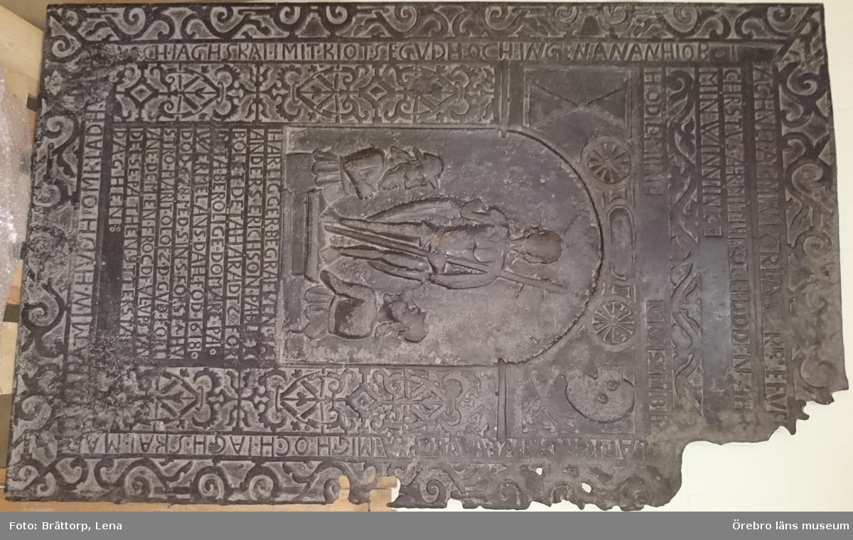 """""""Domarens gravhäll""""Över Anders Eriksson på Bleksbolet (Blecksberg) död 1678.  Av gjutjärn med reliefframställning av Kristi uppståndelse samt inskrift: HÄR LIGGER BEGRAFVEN SÅ ANDERS ERICSON PÅ BLEX BOLET DETA  HÄRADTZ FÖRDETA BERÖM LIGE DOMARE PÅ WERMELANS DAHL  FÖD 1618 DÖD 1678 MED SIN S FÖRSTA HVSTRO MARGIT OLOFZ D GVD FÖRLÄNE DEM EN FRÖGDEFVL VPSTÅNDELSE PÅ THEN YTTERSTA DAGHEN:  Anders Eriksson Margit Olofsdotter Värmlandsdal  Mått: 1,71 m x 1,07 m"""