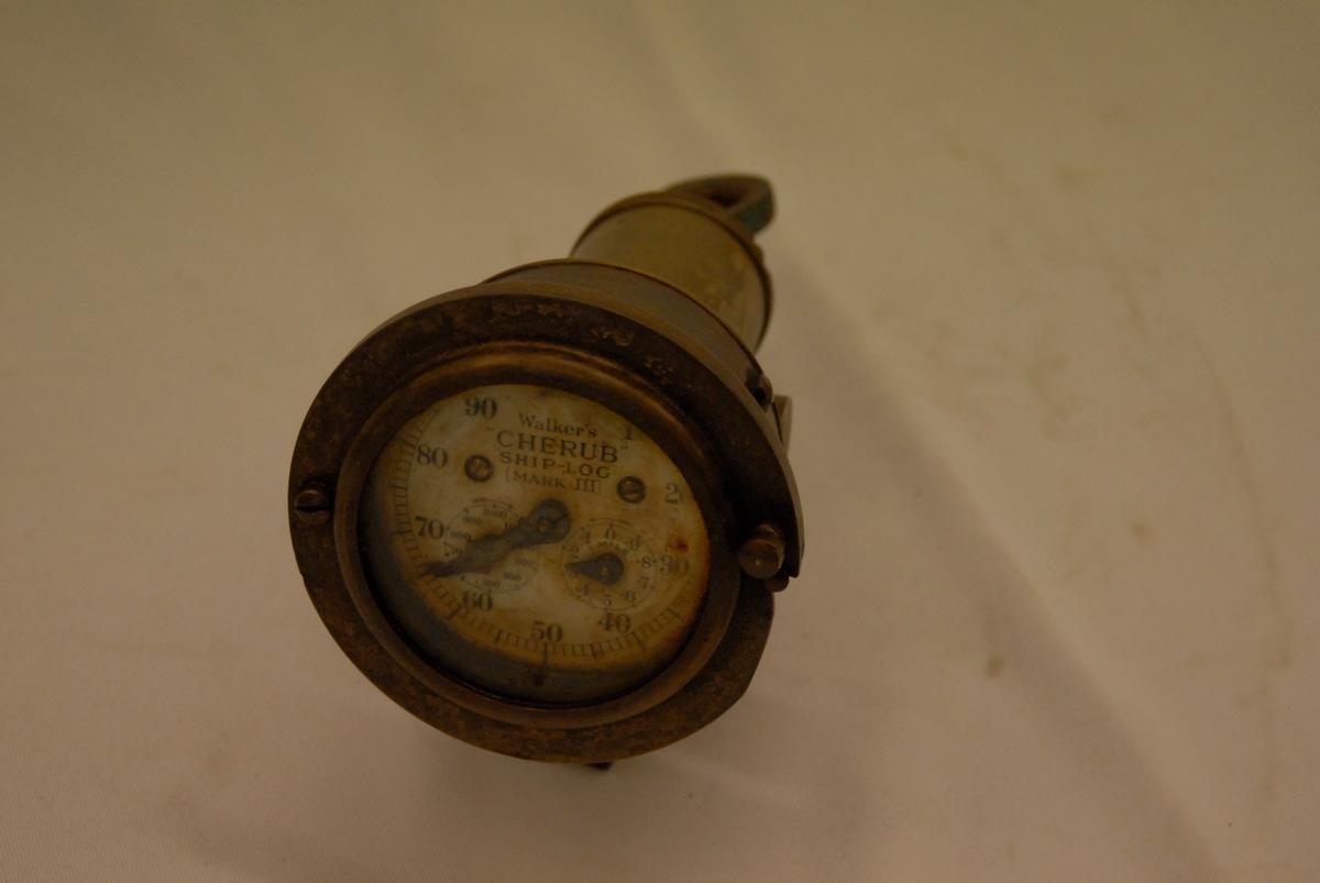 Sirkelforma instrumentskive med visar. Gjenstanden er ein del av eit navigasjonsinstrumentet. Ei line og ein gjenstand i enden av lina høyrer med for at navigasjonsinsrumentet skal fungera.