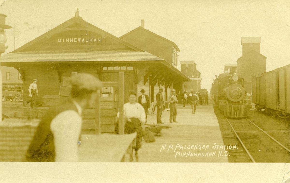 Postkort med motiv fra Minnewaukan passenger station. Bildet viser stasjonsbygningen, toget som står på stasjonen og flere passasjerer/personer på perrongen.