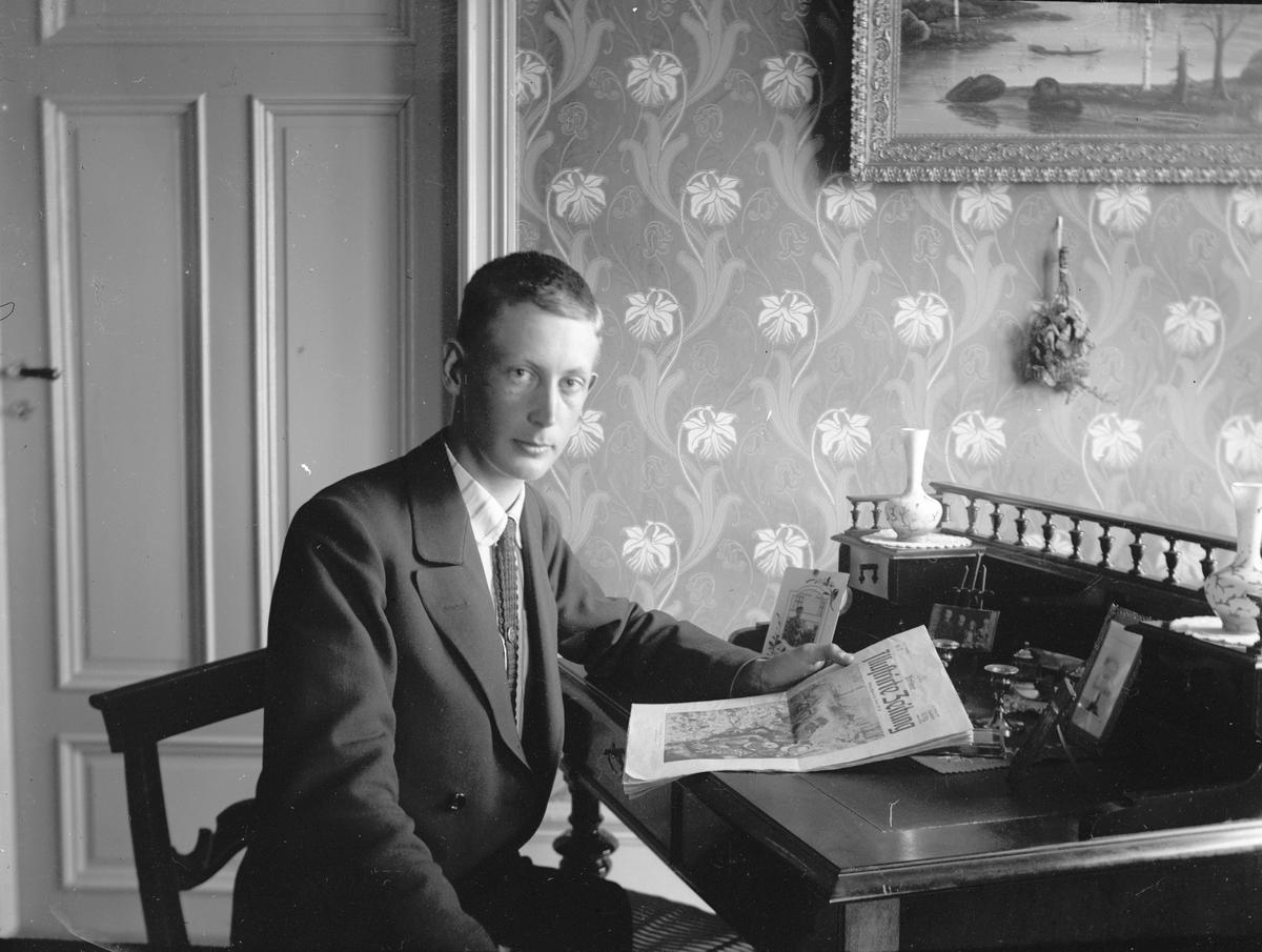 Läser en tysk tidning. Tidsomfånget är 1900 - 1940