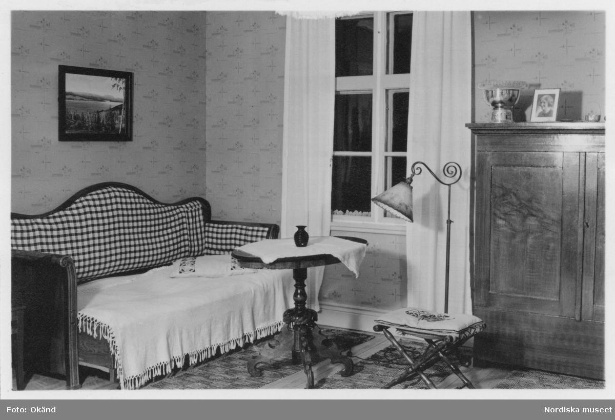 Interiör från Hildegard Hanssons hem i Jämtland. Möblemanget består av en utdragssäng, ett pelarbord och ett skåp. Fotot ingick i pristävlingen Mitt Hem 1942, som var ett samarbete mellan Skolradion och Nordiska museet.