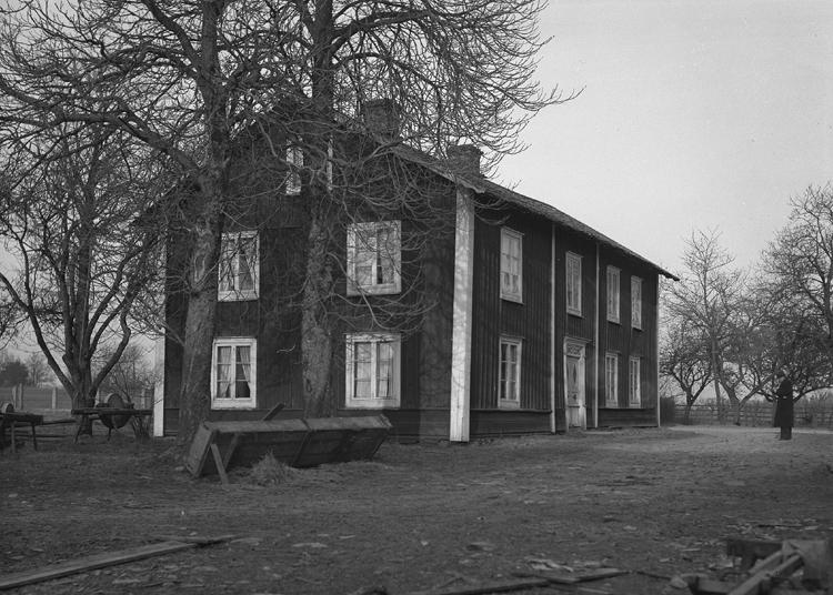 Foto av gästgivaregården i Hössjö. Västra gården, riven 1942. Till höger syns en mörk välklädd man med hatt.