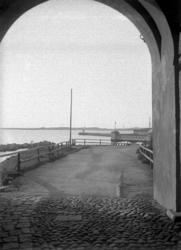 Vy från en av fästningsportarna mot hamnen och kallbadhuset,