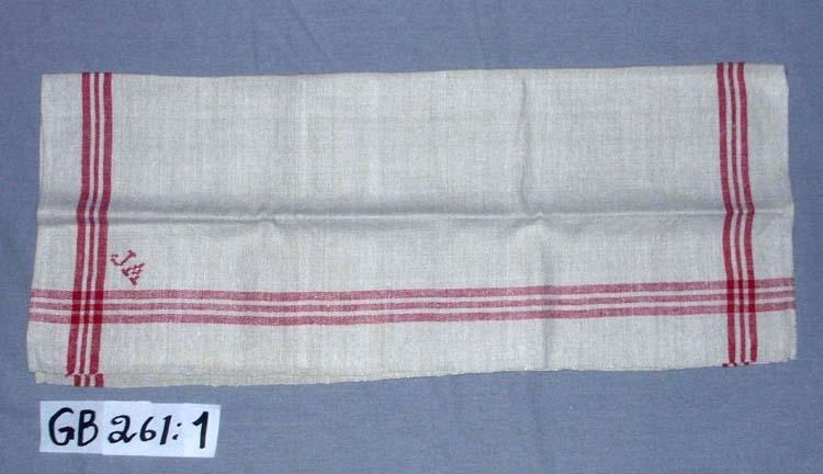 Handduk. Handvävd. Kvalitet: lingarn samt rött bomullsgarn i bårder. Varptäthet: 10 tr/cm. Monogram: J A, sytt i korsstygn, rött. Fållar: 0,6 cm, handfållade. Hängband: handvävda, 2st . 0,7 cm breda, vita med röd rand.  Ett band vitt, 0,4 cm brett. Fastsydda för hand.  Varpordning till bård: Rött:    8 6 8 Oblekt:  4 4 Inskrivet i huvudkatalogen 1996-1997.