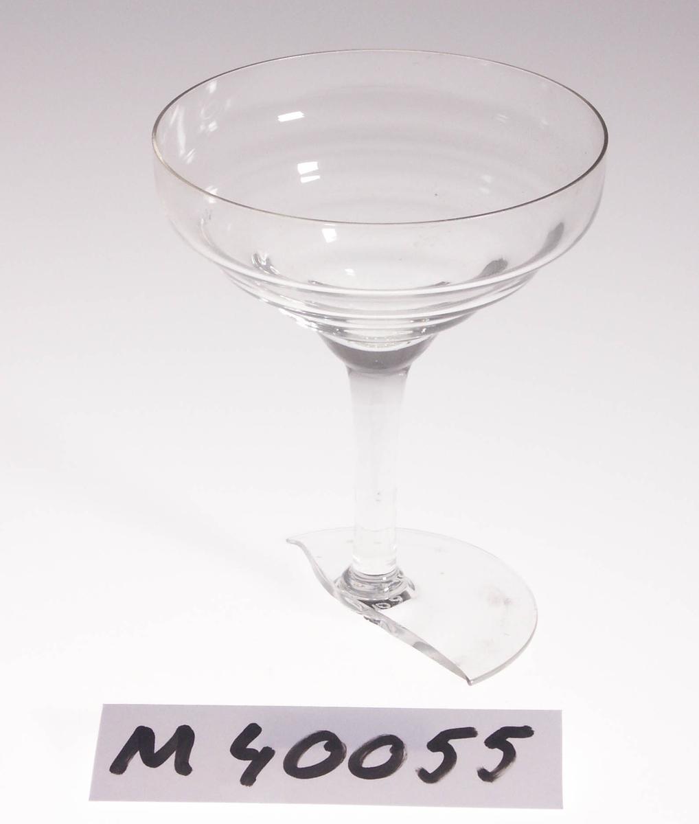 """Champagneglas.  Formgivet av William Stenberg. Ritat 1933-1936. Vågig kupa och stråben. Ofärgat klarglas. Ovan angivna mått avser övre diameter. Fotdiameter: 75 mm. Etikett med text. Se """"Signering, märkning"""" ovan. Inskrivet i huvudkatalogen 1980.  William Stenberg (1885-1961), disponent m.m., Gullaskruv.  SAKNAS. 2013-03-04 Funktion: Champagneskål"""