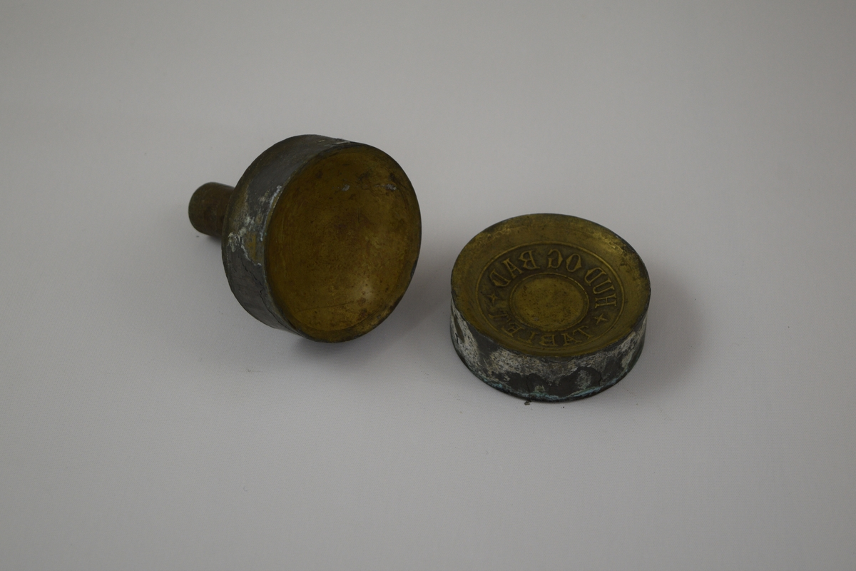 Rund såpeform i to deler for produksjon av såper ved Saanums Sepefabrikk AS i Mandal. Sannsynligvis jern med messing utenpå.  Konkav topp (A) og bunn (B) med relieff/motiv/tekst for trykk. Ulik motiv/tekst i topp og bunn.