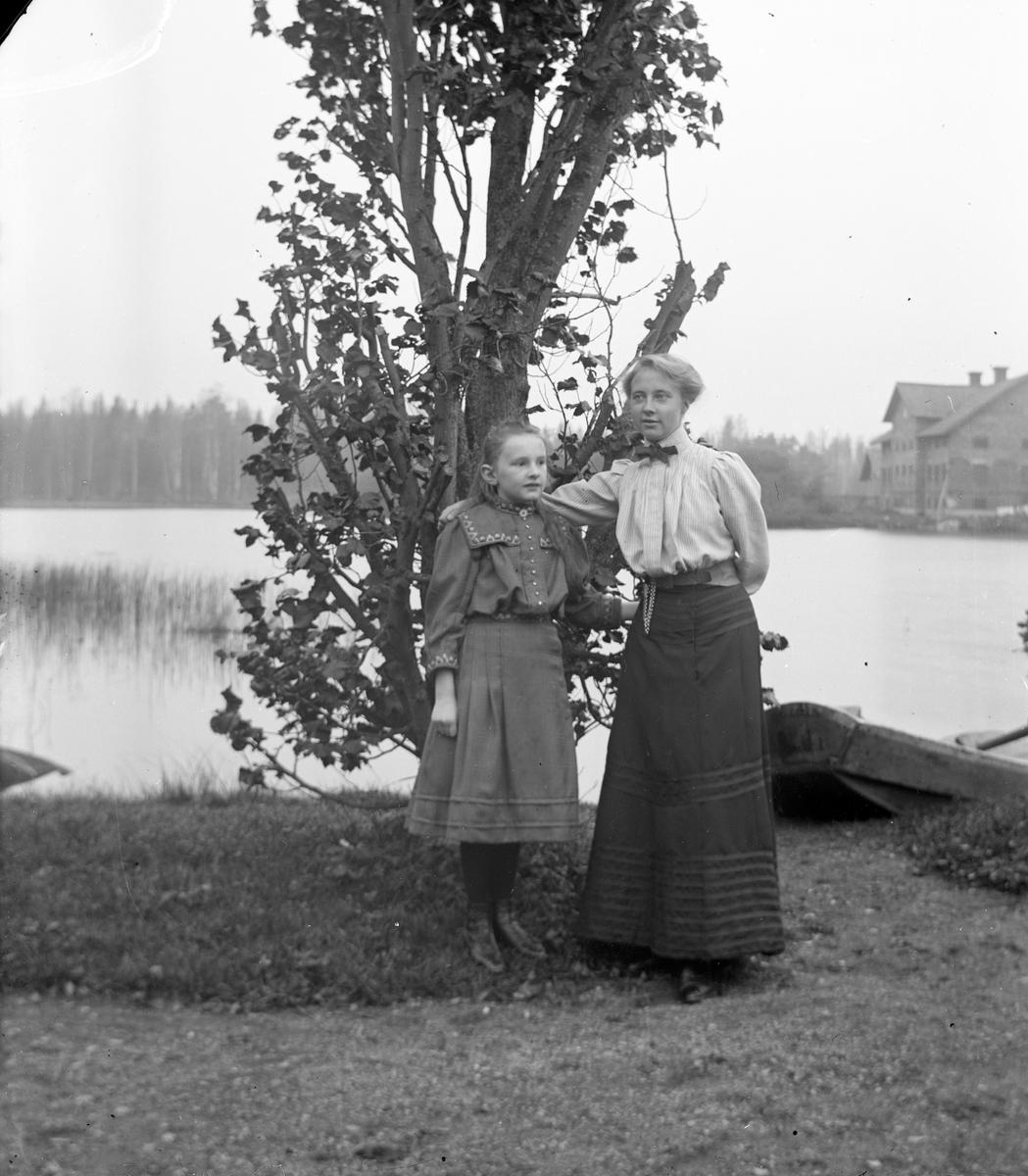 Kvinna och flicka vid stranden. Bilden tagen mot nedre dammen och tegelmagasinet i Gammelstilla, Torsåker.