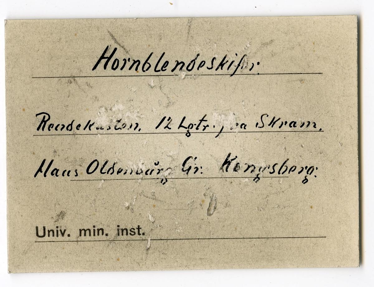 To etiketter i eske:  Etikett 1: Indlagte er fra Rendekasten 12 Lt. fra Skram  Etikett 2: Hornblendeskifer Rendekasten, 12 Lgtr. fra Skram. Haus Oldenburg Gr. Kongsberg.