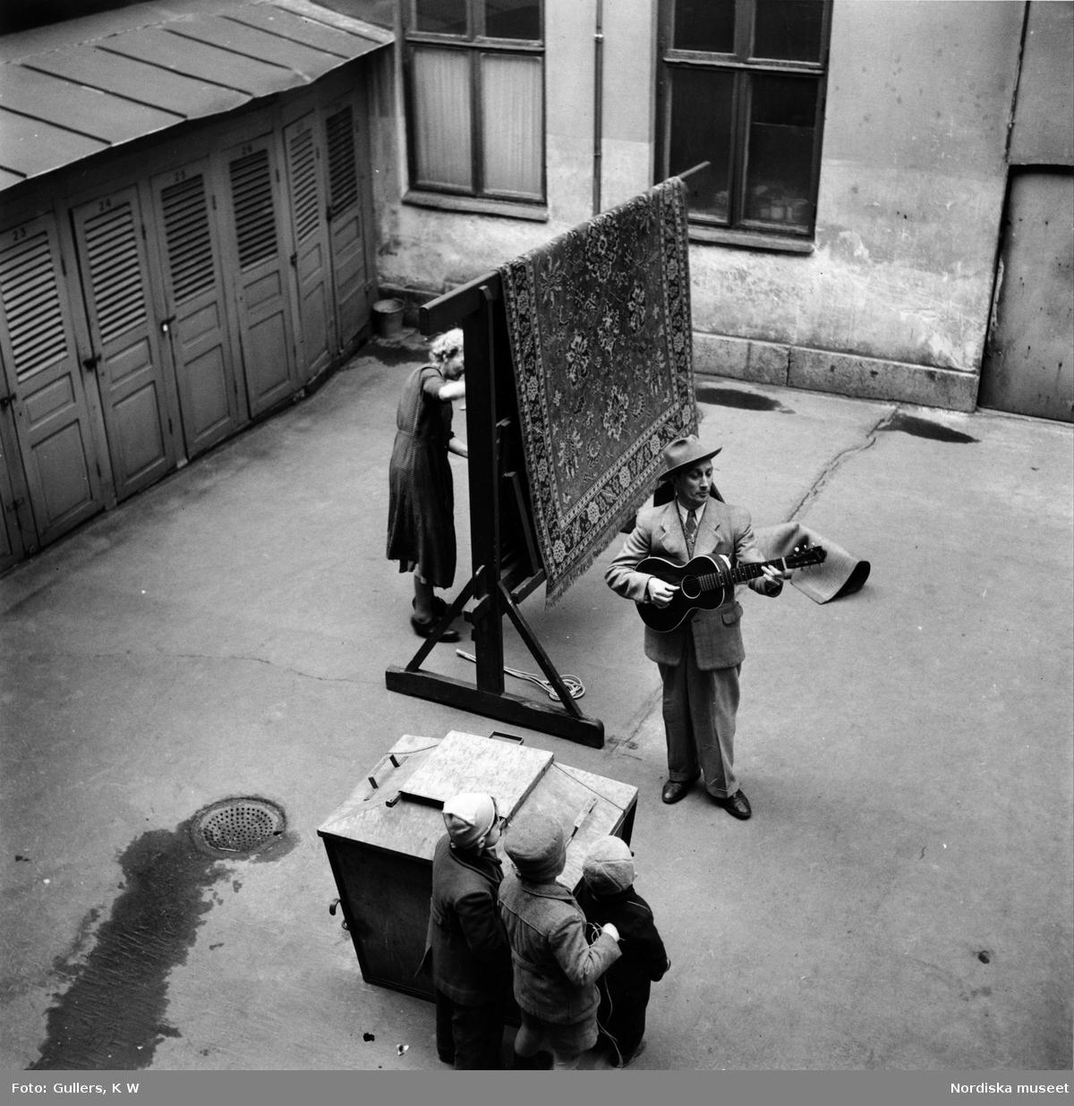 En trubadur spelar gitarr och sjunger på en bakgård i Stockholm inför en publik av barn. Intill ägnar sig en kvinna åt mattpiskning.