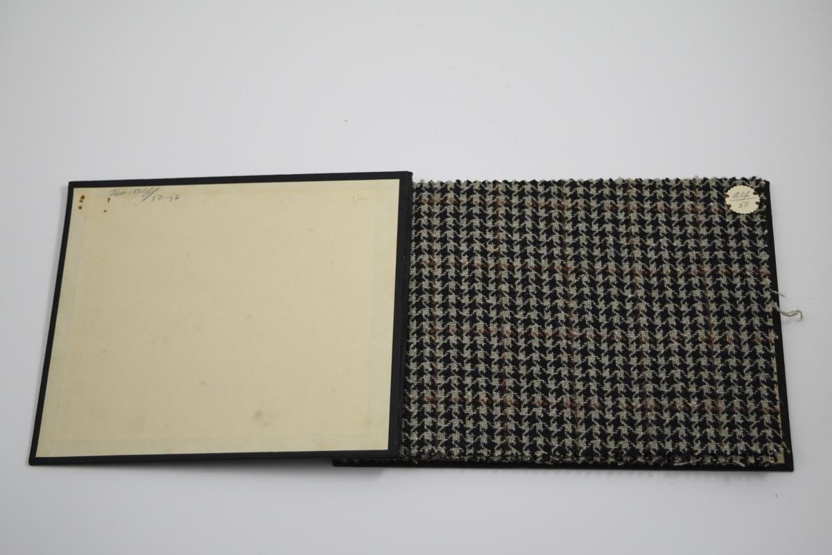 """Prøvebok med 7 prøver. Middels tykke stoff med avansert mønster. Stoffene er merket med en rund papirlapp, festet til stoffet med metallstifter, hvor nummer er påført for hånd. Påskriften på innsiden av forsideomslaget viser at alle stoffene har kvalitet """"Alf"""".   Stoff nr.: alf/50, alf/51, alf/52, alf/53, alf/54, alf/55, alf/56."""
