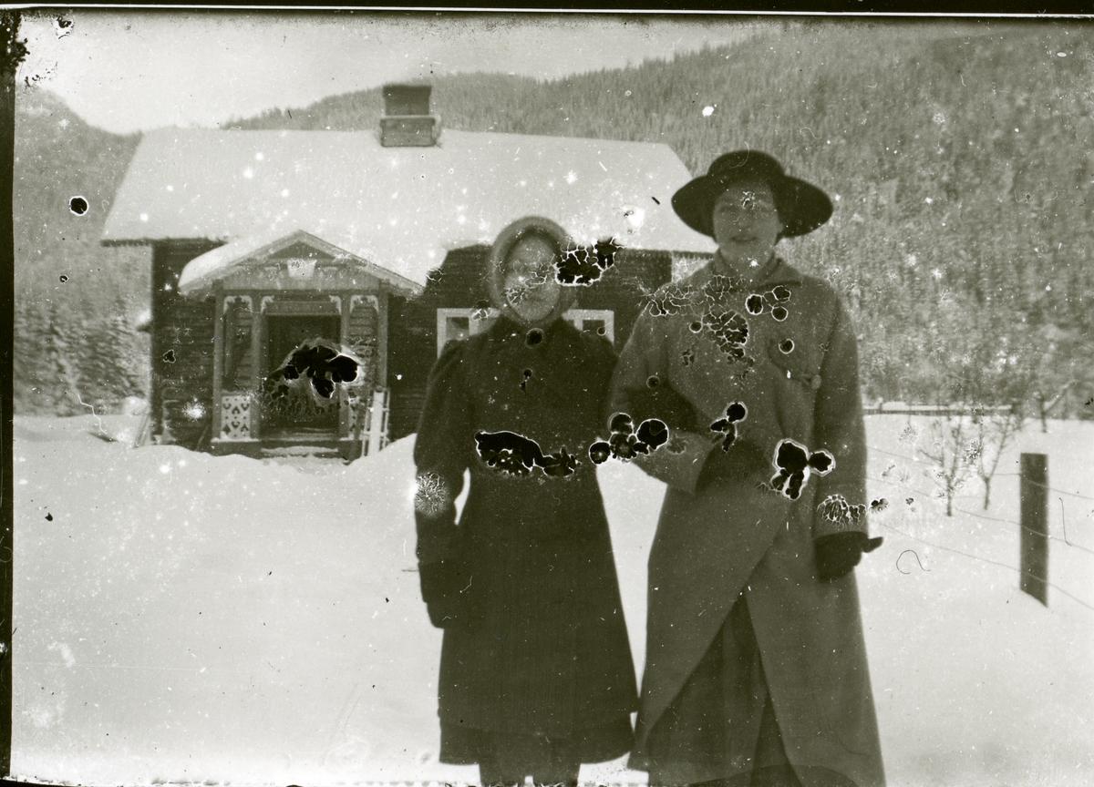 Olga og Jørgine Smedmoen. Smedmostuga i bakgrunnen.