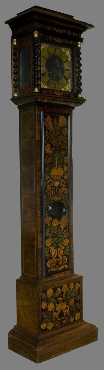 Golvur med fodral av ek fanérat med  bl.a. valnöt och valnötsrot. Hög rektangulär modell på utkragad nederdel.  Rakt avslutad huv med kraftigt listverk och spiralvridna hörnkolonnetter av ebenholtz, upptill och nedtill förgyllda. Huven har tre öppningsbara glasade luckor. Urverk med pendel och lod, kvadratisk urtavla av metall med förgyllda hörnbeslag. Sifferring med romerska siffror, visare av blånerat stål. Fodralets framsida har rik intarsiadekor, s.k. bloemenmarqueterie av engelsk-holländsk typ, med inläggningar i färger av olika träslag med blomsterurna, växter, tulpaner och andra blommor, fåglar m.m. På dörrens framsida ett glas i en liggande oval träram. Sidorna med inramning av stående fält.  Insidan svartmålad.  Graverad signatur på sifferringen: Jacobus Markwick, (eller Markwich) Londini.