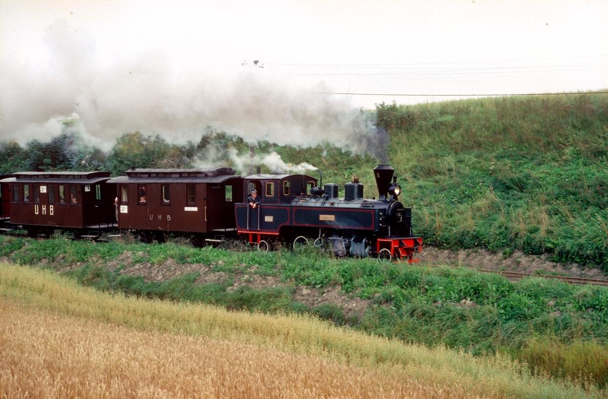 Lokomotivfører Finn Halling på damplokomotiv nr. 6 Høland med museumstog på Urskog-Hølandsbanen, Tertitten. Vi ser vognene CF11 og C12, to toakslede vogner anskaffet fra Polen til museumsbanen.