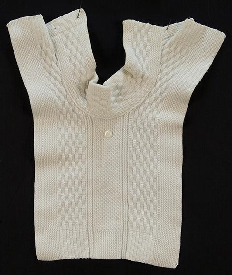 Halslinning med bryststykke, håndstrikket i hvit bomull, med pynteknapp i perlemor. Strukturstrikk, rett og vrang, riller, ruter og perlestrikk. Rektangulært bryststykke. Brukt som kjolepynt/smekke?
