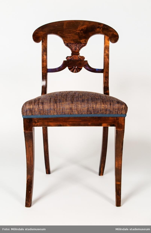 Stol tillverkad av betsad björk. Övre delen av ryggen är utformad som en pelta som bärs upp av ett akantusliknande ornament som i sin tur vilar på en konturerad tvärslå. Under dena finns ett solfjäderonament. De fristående benen är sabelformade. Stoppad fast sits. På baksargens insida är stolen brännstämplad CALAS. Denna modell tillverakdes i tämligen stor omfattning i Lindome på 1820-30-talen.