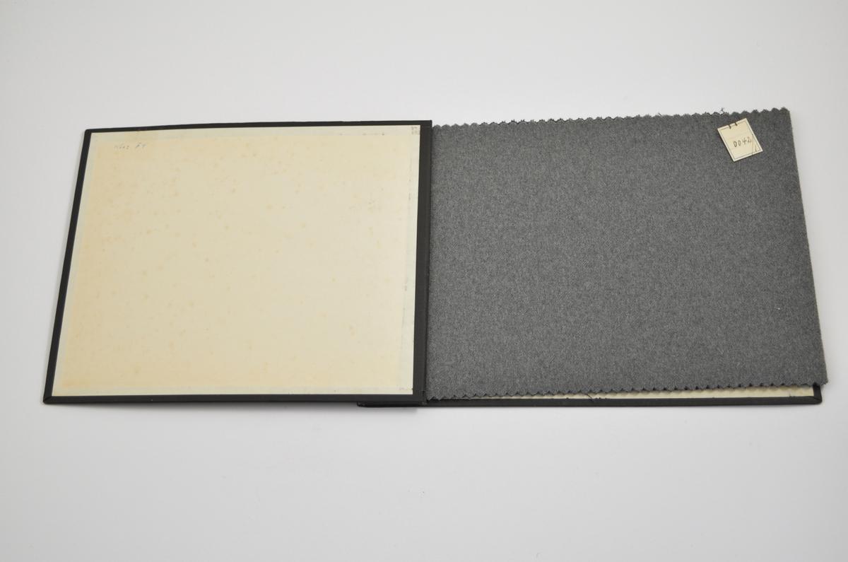 Prøvebok med 2 stoffprøver. Relativt tynne ensfargede stoff. Stoffene ligger brettet dobbelt i boken slik at vranga dekkes. Stoffene er merket med en firkantet papirlapp, festet til stoffet med metallstifter, hvor nummer er påført for hånd.   Stoff nr.: 0042/1, 0042/3