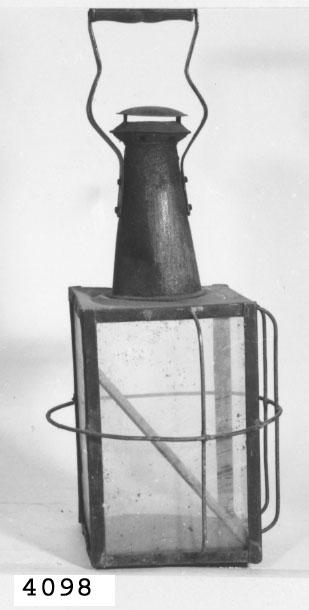 Lykta av järnplåt, fyrkantig. I den glasförsedda fyrkantiga delen finns gejder i botten för insättning av lyse, vilket sker genom att ena glaset lyftes från sin plats (en st. glas saknas). Glasen skyddas utifrån av järntråd (delvis borta). Bärhandtaget av trä och fast vid lyktan.