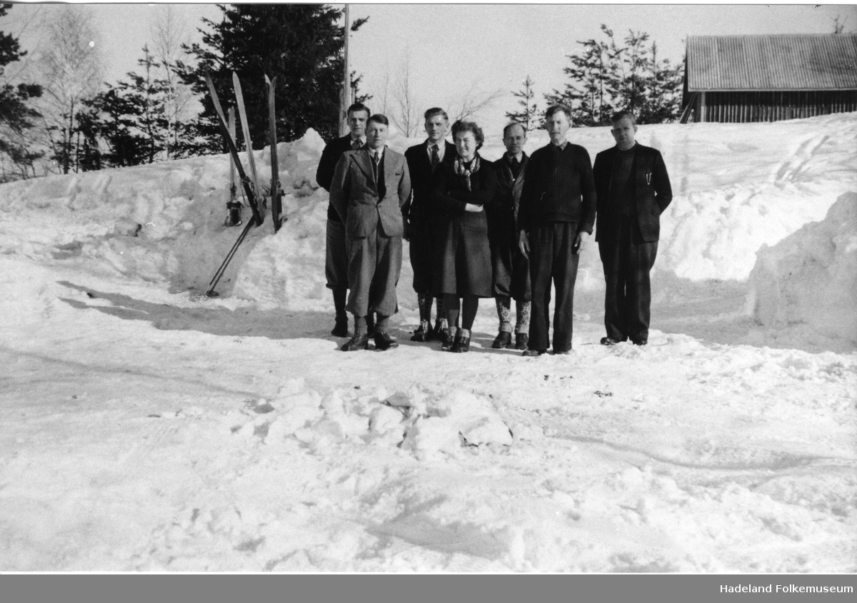 Syv personer står oppstilt ute foran en snøbrøytekant.