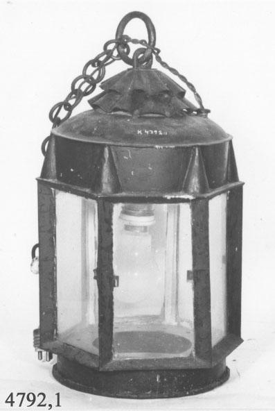 Batterilanterna av modellår 1844. Material: bleckplåt. Sexkantig och grönmålad. Rutor av glas, ring och kätting av järn för upphängning. Lanternan är modifierad och försedd med elektrisk insats.
