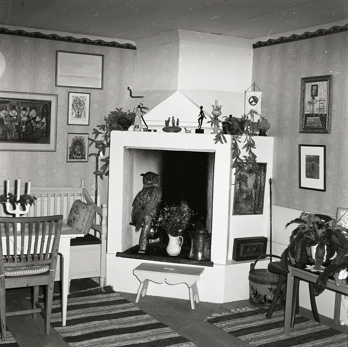 En hemtrevlig miljö har skapats genom textiler, prydnader och blommor i salen på gården Sunnanåker. Rummets hjärta är den öppna spisen som också är bildens fokuspunkt. En uppstoppad uggla står i eldstaden vilket inte förvånar då naturfantasten Hilding Mickelsson residerar i huset.