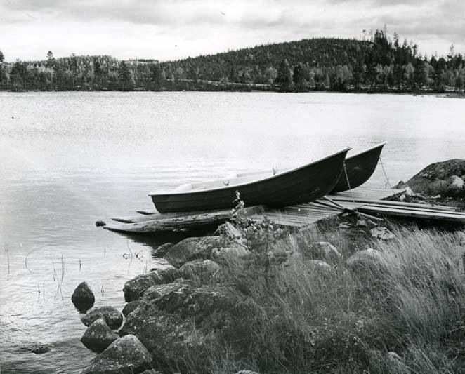 Två roddbåtar ligger uppdragna på en brygga och är förtöjda.