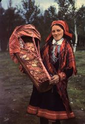 Postkort,  Norsk Folkemuseum. Samisk kvinne med spedbarn i k
