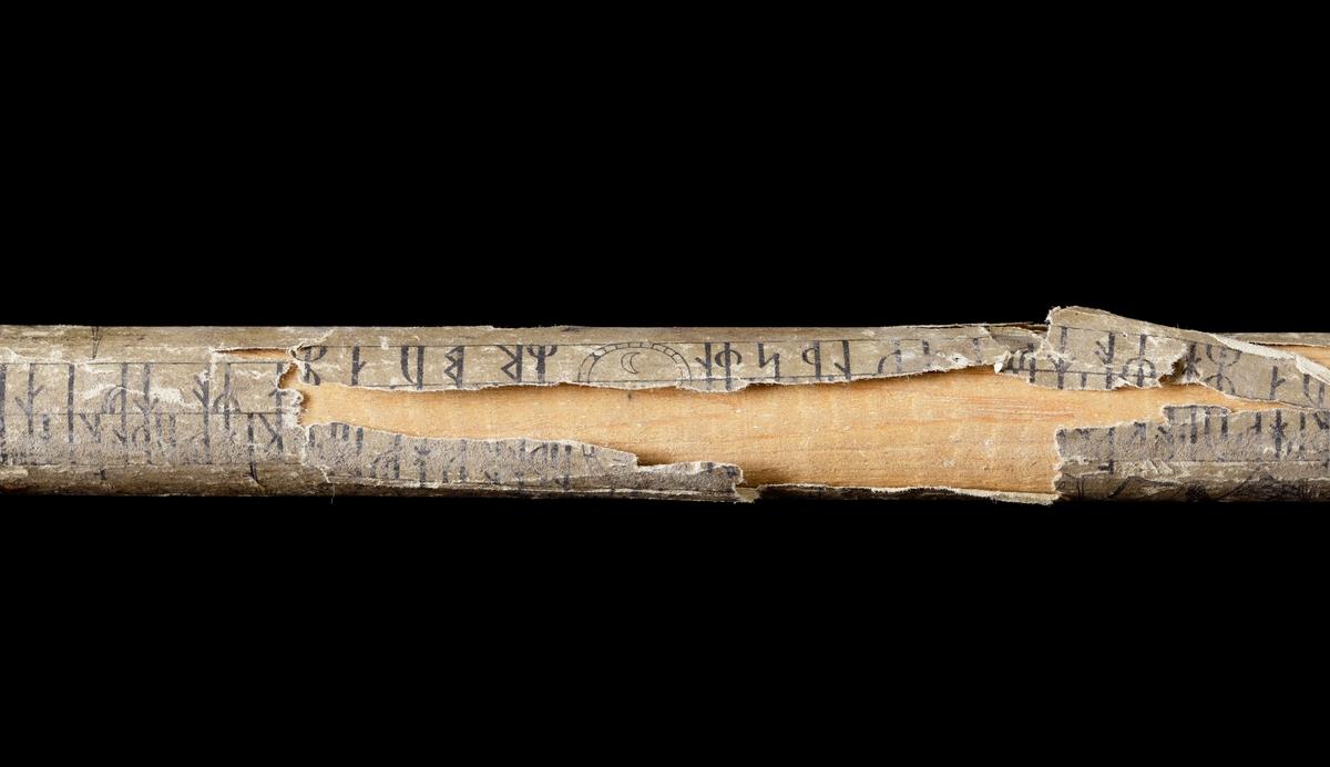 Kalenderstav i form av en rund trästav med en tryckt runkalender i papper, limmad på staven. Den gamla svenska hushållsalmanackan, tryckt 1775 hos Lars Wennerberg, Stockholm.