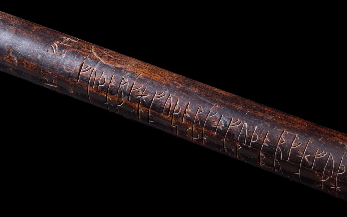 Kalenderstav i form av stavformad runkalender. Rund, av trä. Staven är mörkbetsad, och har en något avsmalnande form. Symbolbilder inskurna.