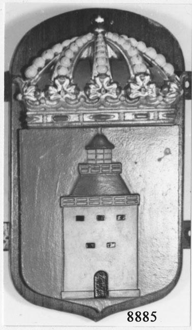 Båtemblem av gjuten mässing. På en platta av mahogny. Minsveparen Landsorts vapen, bestående av kunglig krona och därunder en fyr.