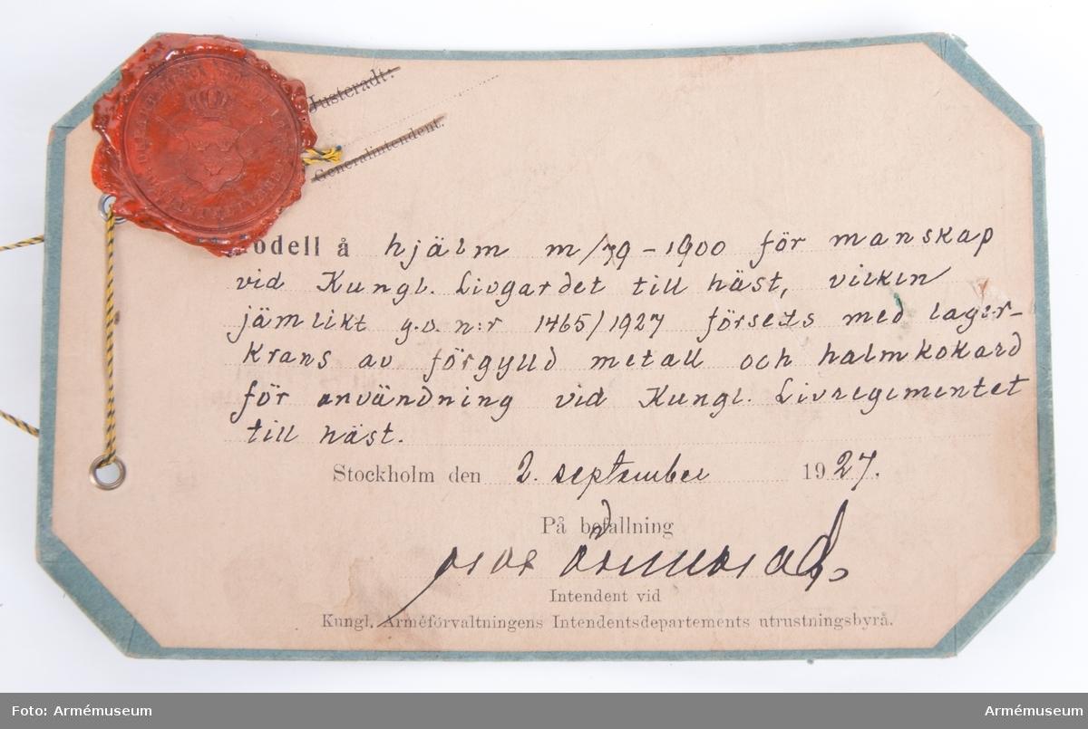 """Grupp C I.  Text på modellappen lyder: """"Modell å hjälm m/79-1900 för manskap vid Kungl Livgardet till häst, vilken jämlikt g.o. nr 1465/1927 försetts med lagerkrans av förgylld metall och halmkokard för användning vid Kungl Livregementet till häst. Stockholm den 2 september 1927."""""""