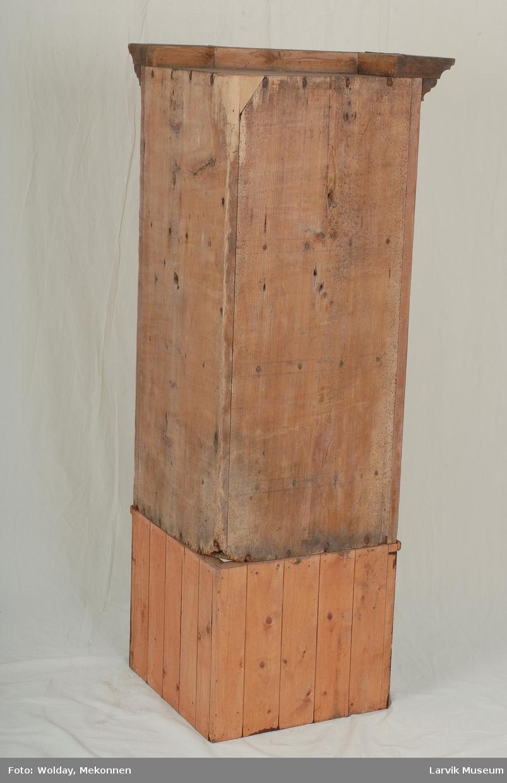 Form: bred prof. topplist,forside i tre flater,dør med skuff under, to hyller i skapet, feltinndeling med profilert rødmalt listverk på dør og sideflater,lås med jernbeslag.