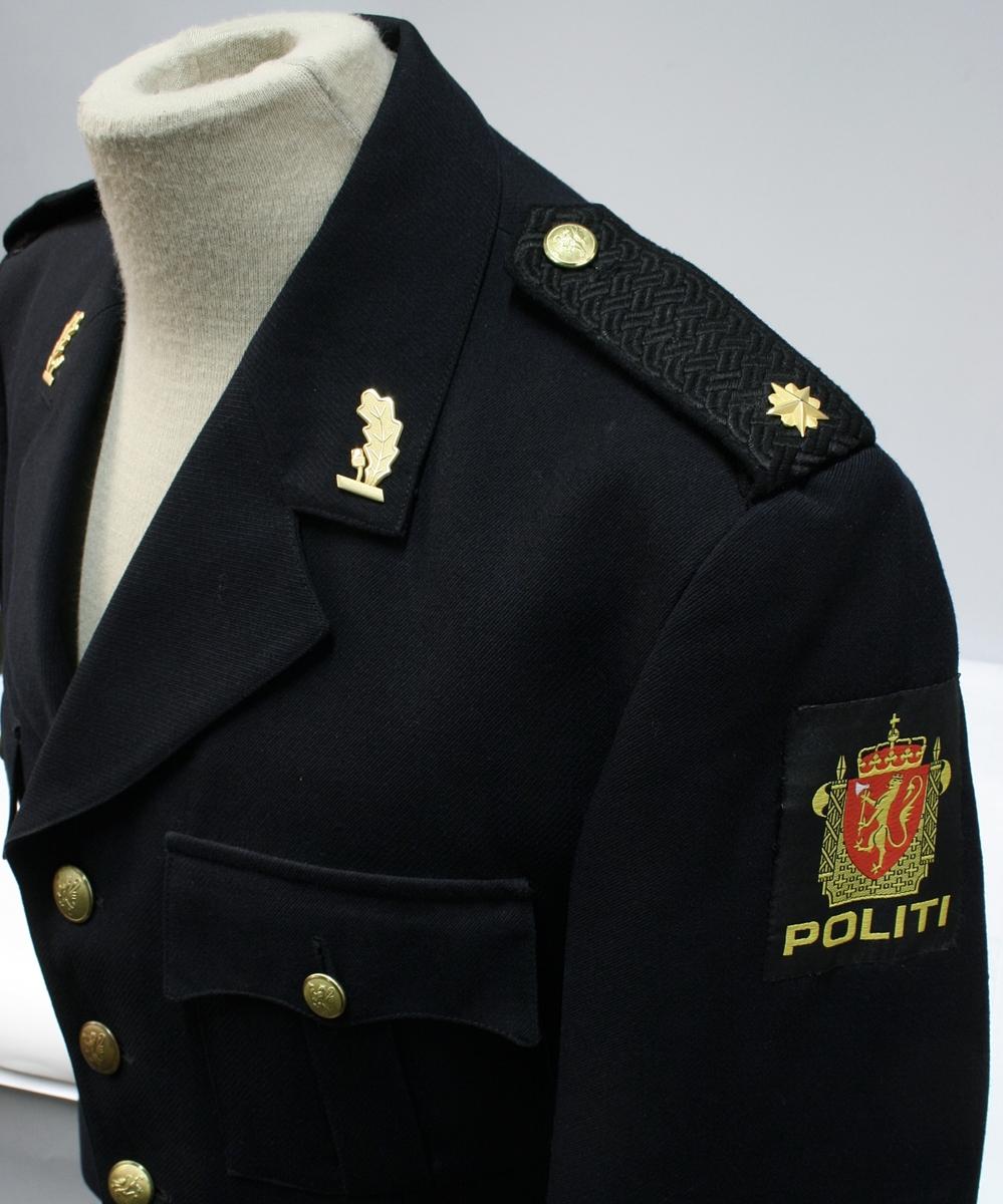 Enkeltkneppet jakke med fire riksløveknapper, fire ytterlommer, ekeblad av metall på kragespeil, skulderklaffer med en stjerne, og politimerke på ermet.