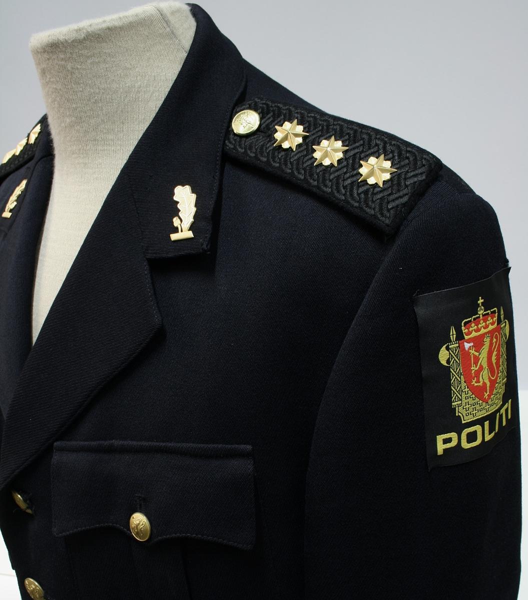 Enkeltkneppet jakke med fire riksløveknapper, fire ytterlommer, ekeblad av metall på kragespeil, skulderklaffer med tre stjerner, split og to knapper bak, og politimerke på ermet.